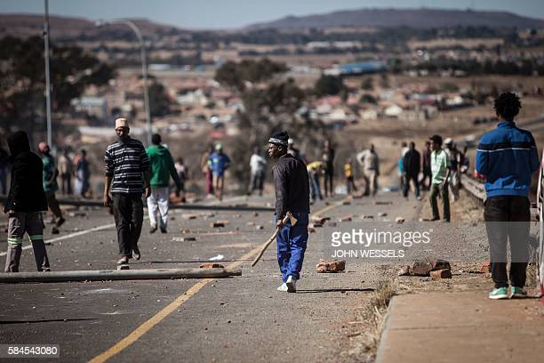 TOPSHOT A man armed with an axe walks after a service delivery protest turned violent between two communities clashing over a suspected electricity...