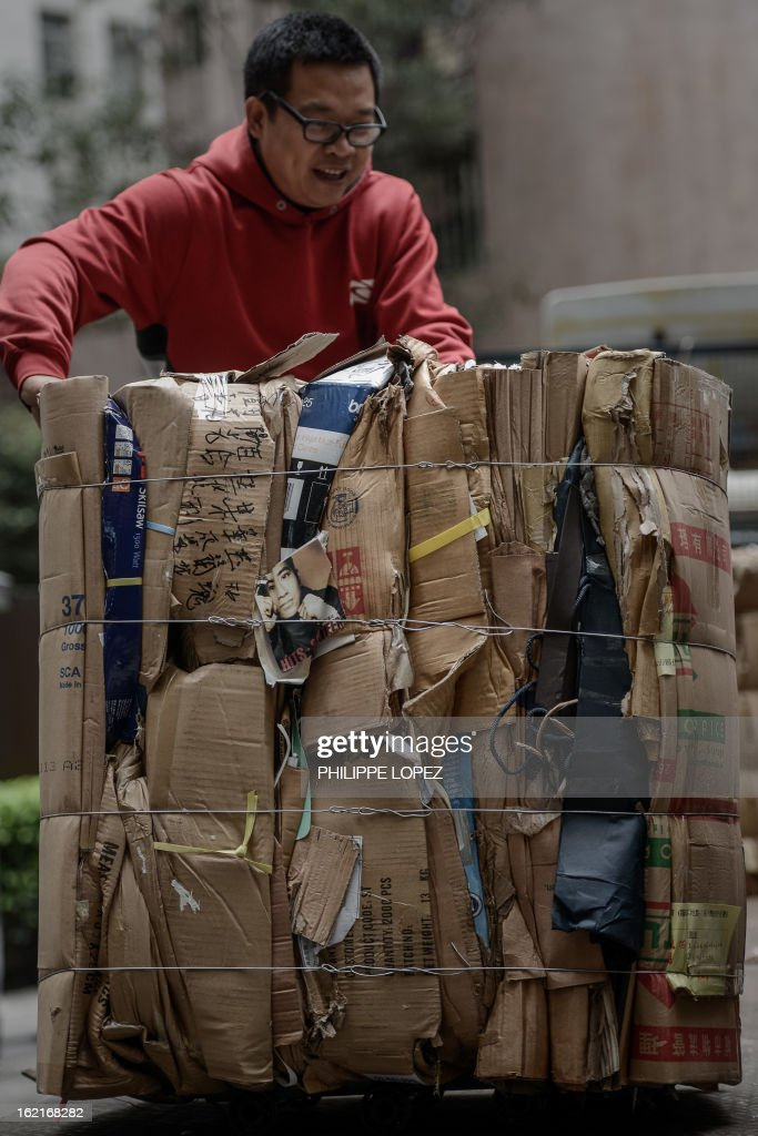 A man arranges a stack of compressed cardboard to be recycled in Hong Kong on February 20, 2013. Activists have claimed for years that Hong Kong lags behind the rest of the world on environmental issues ranging from recycling to lanes for cyclists. AFP PHOTO / Philippe Lopez