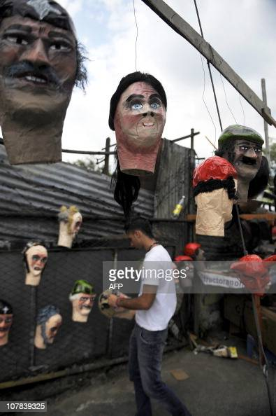 A man arranges 'Ano viejo' doll heads in the streets of Cali department of Valle del Cauca Colombia on December 31 2010 These dolls made of cardboard...