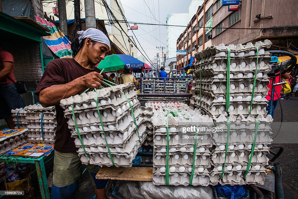 A man arranges cartons of eggs at a stall at the Divisoria market in Manila, the Philippines, on Tuesday, Jan. 22, 2013. Philippine government bonds advanced on speculation the central bank will hold its benchmark interest rate at a record low at a meeting tomorrow, supporting demand for the nation's debt. Photographer: Julian Abram Wainwright/Bloomberg via Getty Images