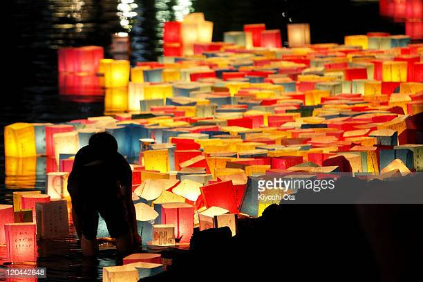 A man arranges paper lanterns released onto the Motoyasu River to commemorate the atomic bomb victims and pray for world peace beside the ABomb Dome...