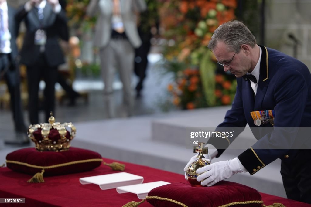 A man arranges the regalia (Crown, Sceptre, Globus Cruciger and Sword of State) at the credence-table prior to the inauguration of HM King Willem Alexander of the Netherlands and HRH Princess Beatrix of the Netherlands at New Church on April 30, 2013 in Amsterdam, Netherlands.