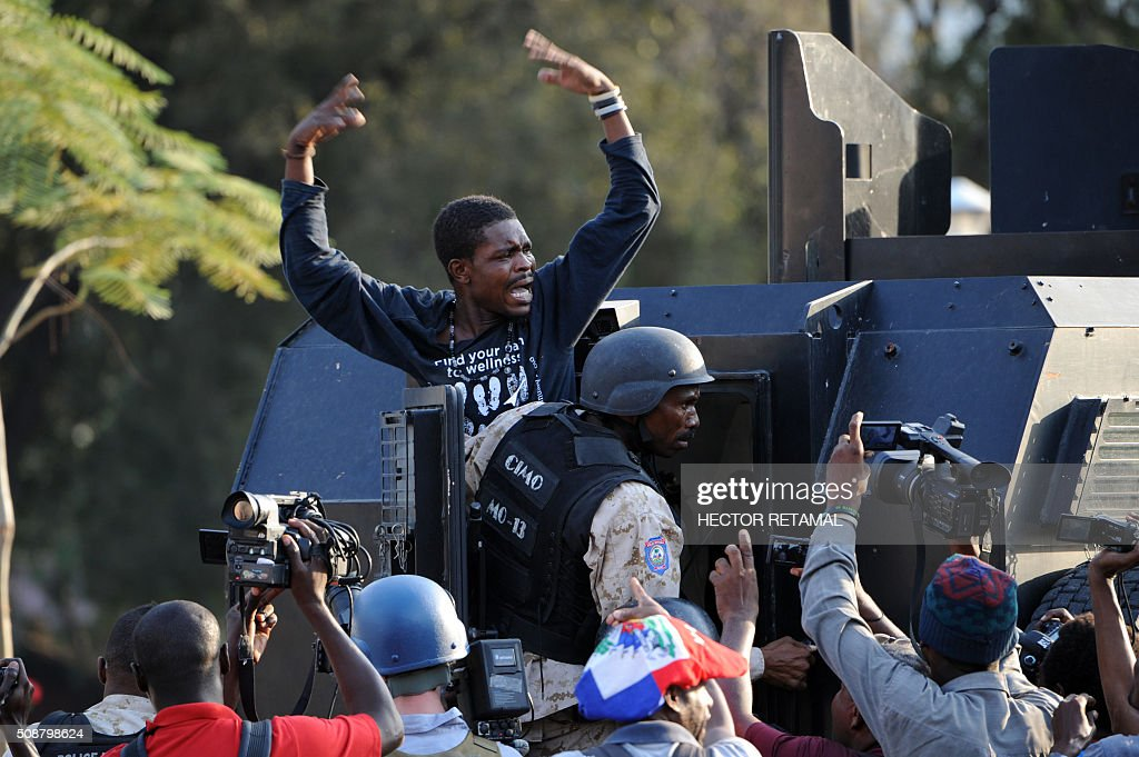 A man arrested by Haitian police asks for help during a protest by opposition demonstrators against Haitian President Michel Martelly, in Port-au-Prince, on February 6, 2016. Haitian politicians inked a last-minute agreement to install a transitional government, just hours before President Michel Martelly was scheduled to step down with no replacement in line. / AFP / HECTOR RETAMAL
