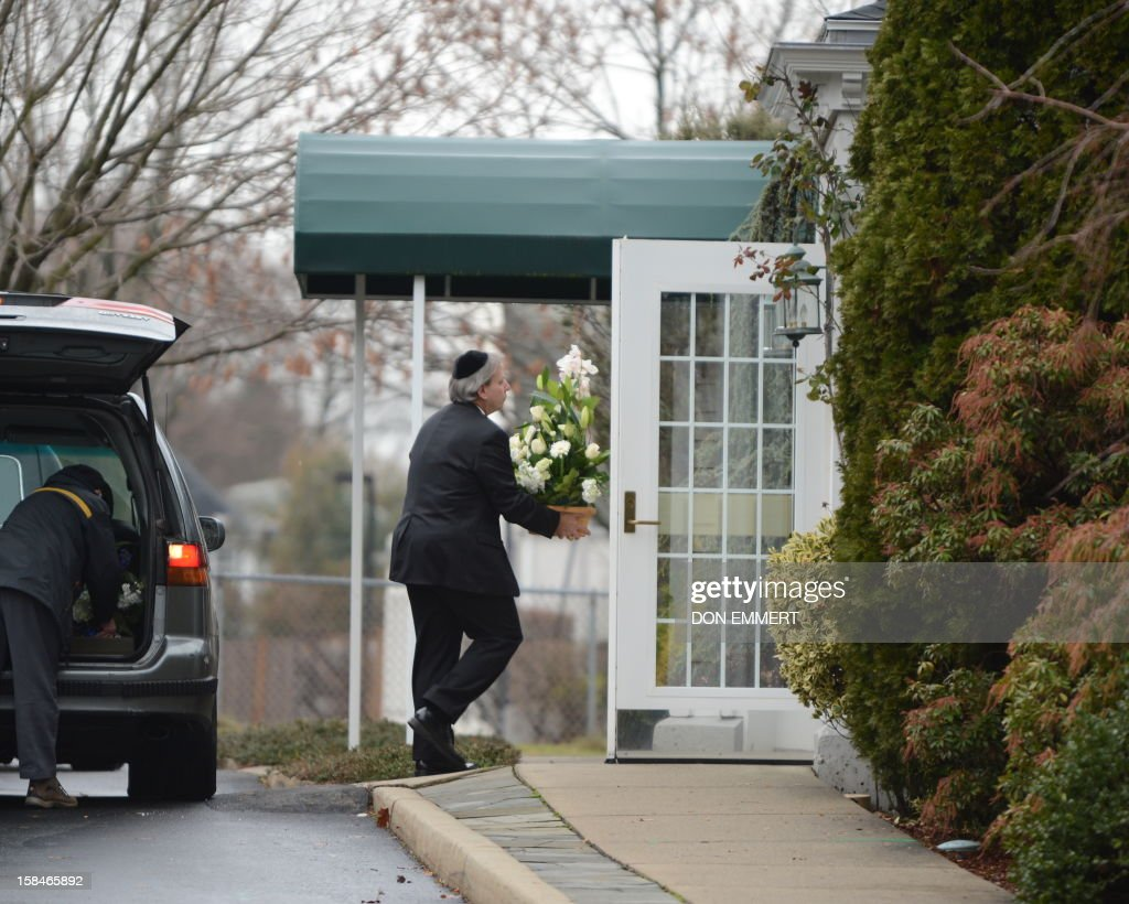 A man arrives with flowers at Abraham L. Green and Son Funeral Home in Fairfield, Connecticut, December 17, 2012 for Noah Pozner,6 one of the victims of the elementary school shooting in Newtown, Connecticut. Funerals began Monday after the school massacre that took the lives of 20 small children and six staff, triggering new momentum for a change to America's gun culture. The first burials, held under raw, wet skies, were for two six-year-old boys who were among those shot in Sandy Hook Elementary School. On Tuesday, the first of the girls, also aged six, was due to be laid to rest. There were no Monday classes at all across Newtown, and the blood-soaked elementary school was to remain a closed crime scene indefinitely, authorities said. AFP PHOTO/Don Emmert