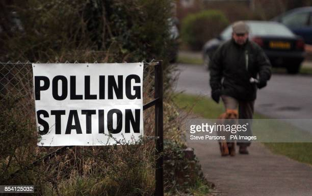A man arrives with his dog at a polling station to cast his vote in the byelection in Eastleigh Hampshire