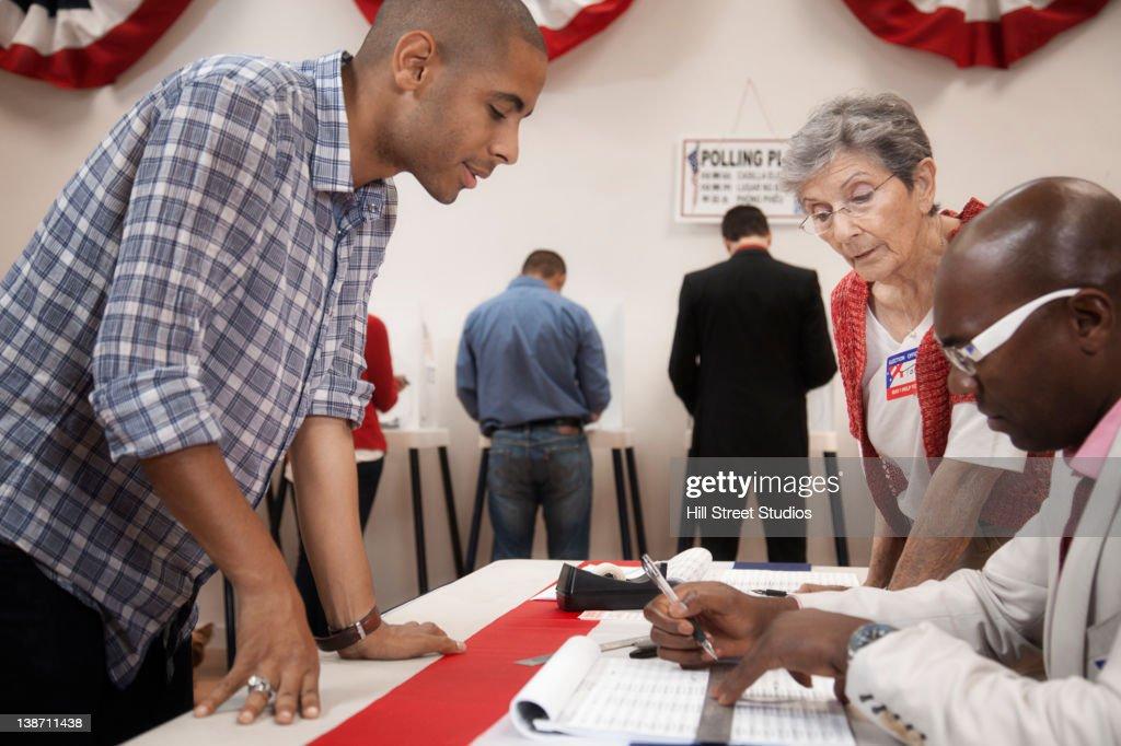 Man arriving at registration desk in polling place