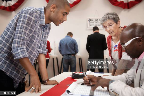 Man arriving at registration desk in polling place