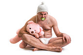 Man as baby. Child in diaper with pink teddy bear sitting on floor - isolated on white.