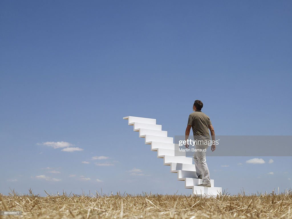 Man ascending stairway to sky : Stock Photo