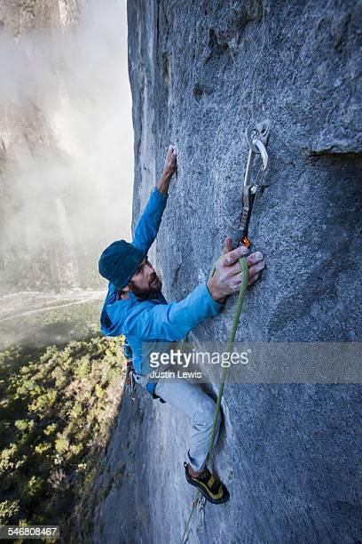 Man Ascends Steep Rock Wall