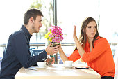 Man asking for forgiveness offering a bunch of flowers to his girlfriend in a coffee shop with an exterior background. Couple problems concept