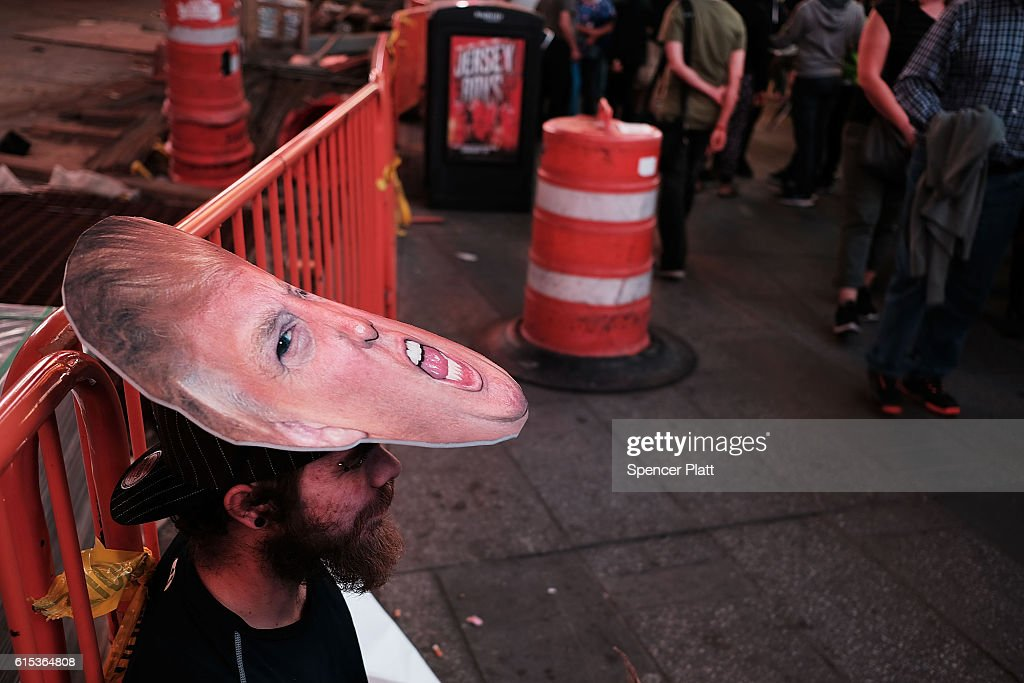 A man asks for tips in Times Square in a Donald Trump mask on October 17, 2016 in New York City. As the nation prepares for the final debate between presidential candidates Donald Trump and Hillary Clinton, America has become transfixed on the issues surrounding the two historic candidates. America will go to the poles to pick the next president on November 8.
