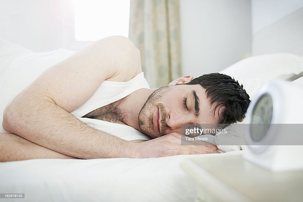 man asleep in bed with alarm clock : Stock Photo