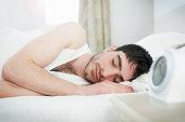man asleep in bed with alarm clock