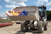 Man asleep in bucket of earth mover