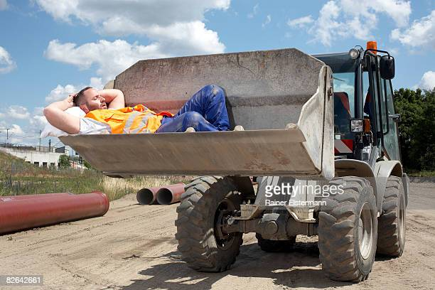 Man asleep in bucket of earth mover