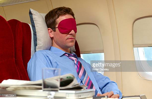 Man asleep in business class on plane