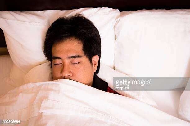 Man asleep in comfortable hotel room bed.