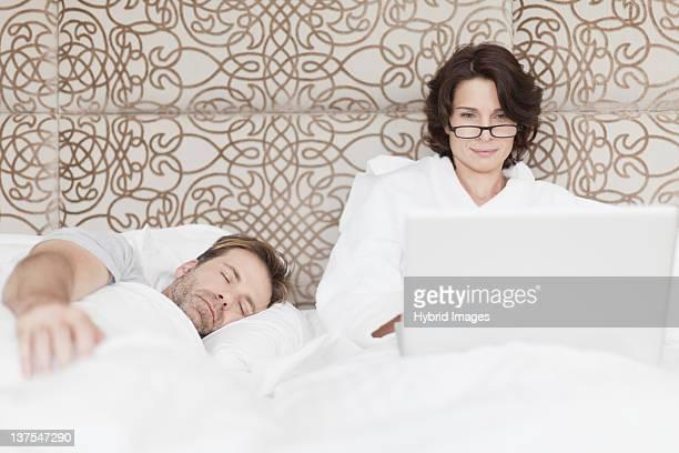 Man asleep next to working girlfriend