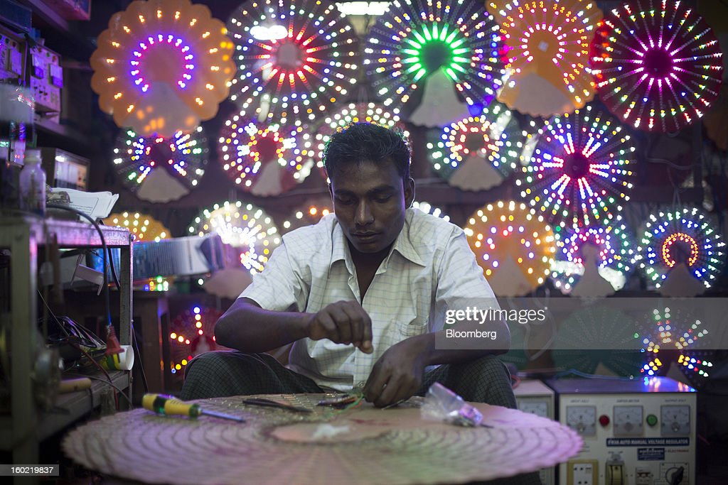 A man assembles a light fixture in a workshop in Yangon, Myanmar, on Tuesday, Jan. 22, 2013. Myanmar cleared about $1 billion in overdue debt with the Asian Development Bank and World Bank using a bridge loan from Japan, opening the door for increased lending as the country seeks to overhaul its infrastructure. Photographer: Brent Lewin/Bloomberg via Getty Images