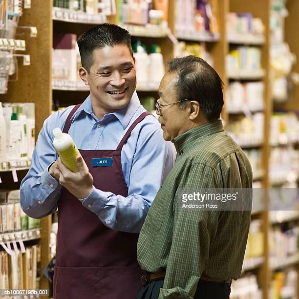 Man assisting senior man in pharmacy, smiling