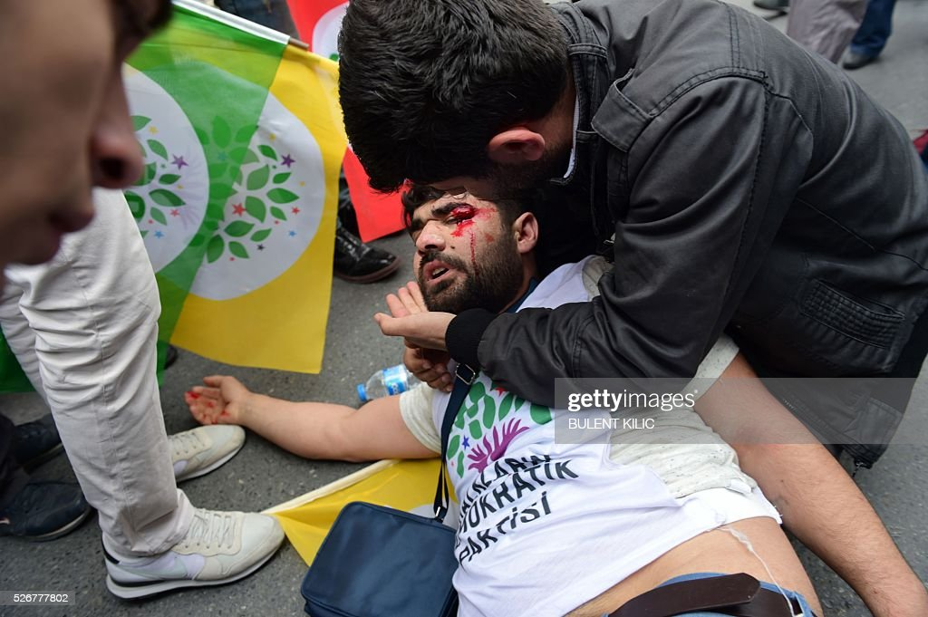A man assists a protestor bleeding from his eye after he was injured during clashes with anti-riot police during a May Day rally in Bakirkoy, a district of Istanbul, on May 1, 2016. Turkish labour activists and leftists marked the annual May Day holiday, with thousands of security deployed and bracing for trouble after the authorities refused to allow protests in central Taksim Square. / AFP / BULENT