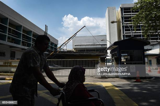 A man assists a woman in a wheelchair outside the forensics wing of the Hospital Kuala Lumpur where the body of Kim JongNam is being held in Kuala...