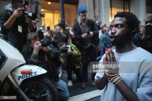 A man associated with the 'Occupy Wall Street' movement prays in front of police vehicles before being arrested in the financial district on October...