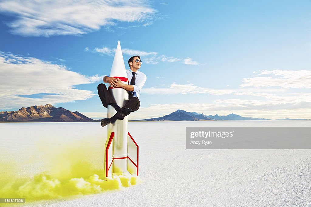 Man astride rocket about to take off.