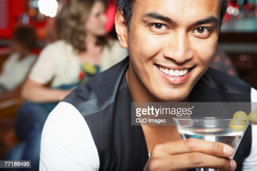 A man at a bar with a drink : Stock Photo