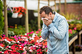 Man sneezing at a greenhouse and suffering from hay fever - spring allergy concepts
