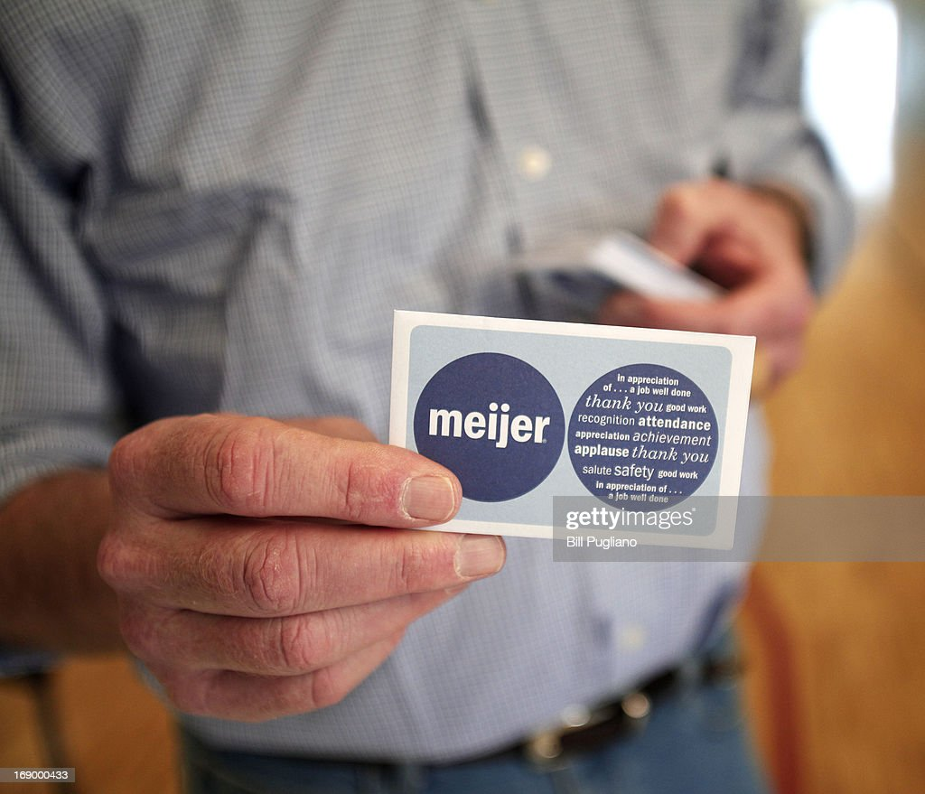 A man at a 'Groceries For Guns' gun buyback program displays a $50 Meijer gift card that people were given in exchange for guns they brough in May 18, 2013 at the New St. Paul Tabernacle Church of God in Christ in Detroit, Michigan. The event was sponsored by the law firm Goodman Acker P.C. in a public-private partnership with Wayne County.