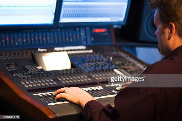 Man at a studio control moving buttons up and down