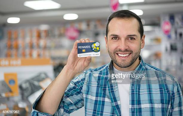 Man at a tech store holding a rewards card