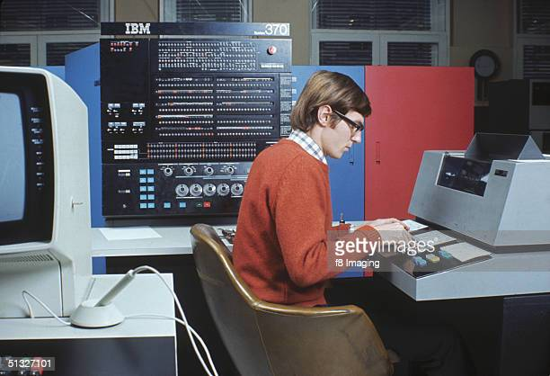 A man at a workstation circa 1970 Behind him is an IBM System/370 mainframe computer Introduced in 1970 it was one of the first computers to include...