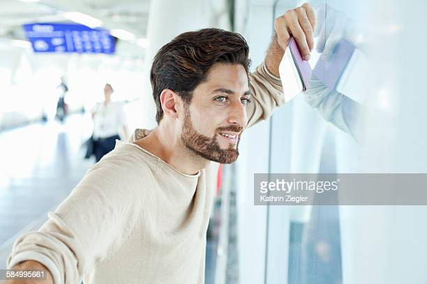 man at airport, looking through window