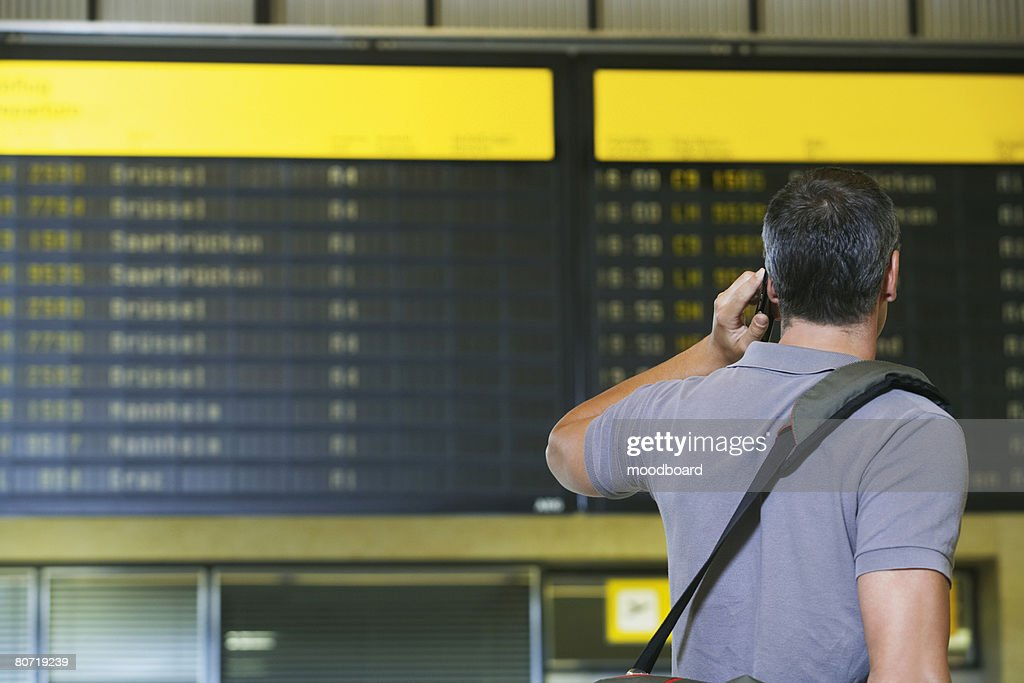 Man at Airport Using Cell Phone