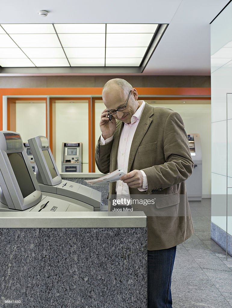 man at ATM, reading statements of account : Stock Photo