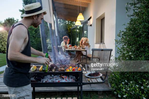 Man at barbecue grill with friends in background
