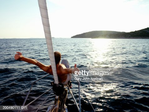 Man at bow of yacht, arms outstretched, rear view : Stock Photo