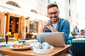 Handsome smiling modern young man using laptop at cafe
