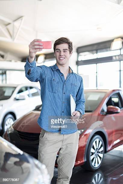 Man at car dealership taking a selfie