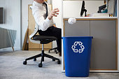 Man at desk throwing screwed up paper into recycling bin