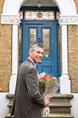 Man at front door with bouquet