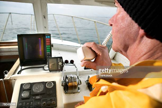 Man at helm of boat with radio