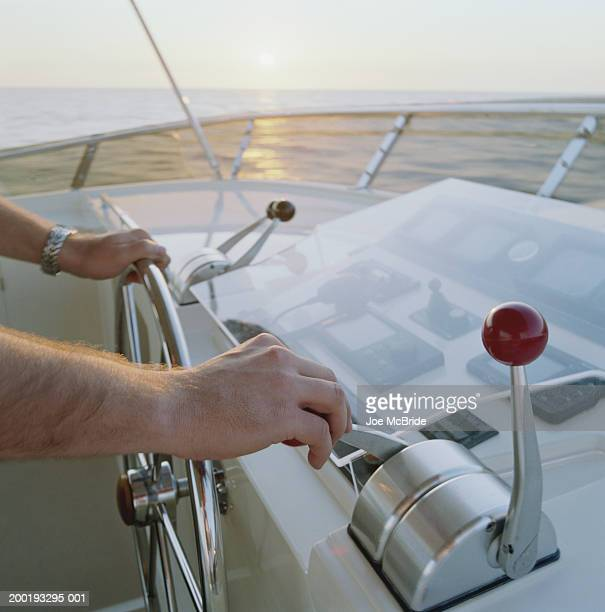 Man at helm of yacht, sunset