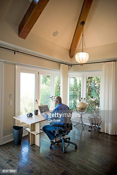 man at his home office desk and computer