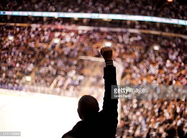 Man at hockey game cheering.