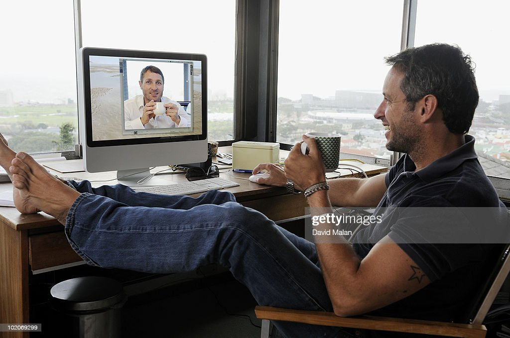 Man at home e-communicating with a friend  : Stock Photo