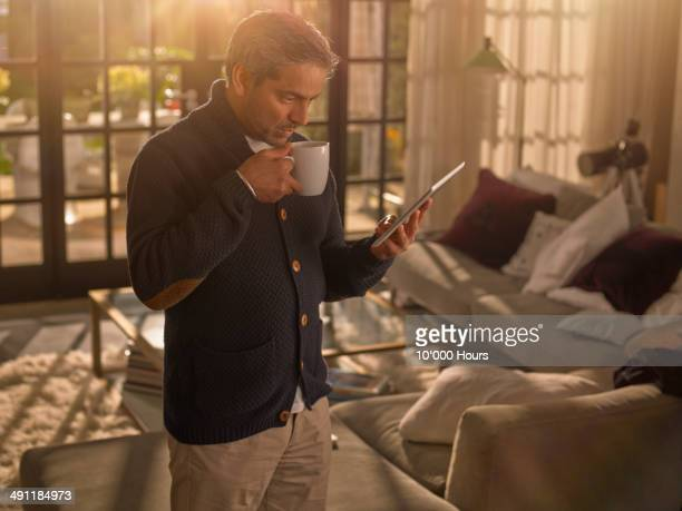 A man at home holding a cup and looking an ipad